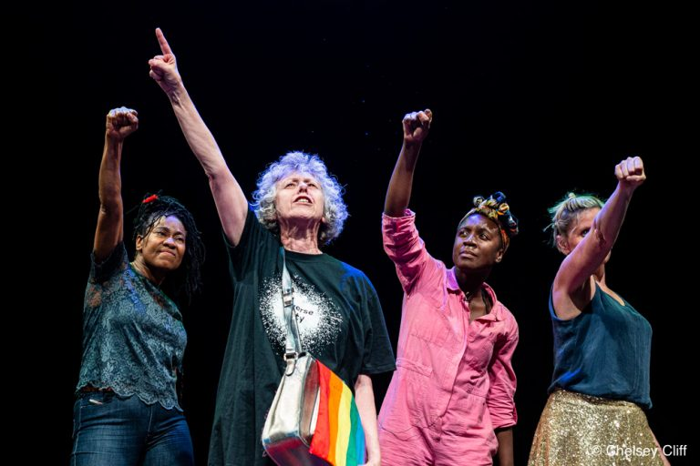 A middle-aged white woman raising her hand above her head on a dark stage, a rainbow-coloured satchel to her side. Behind her, a black middle aged woman and a white middle aged woman and a young black woman. They all hold their hands up in the air.