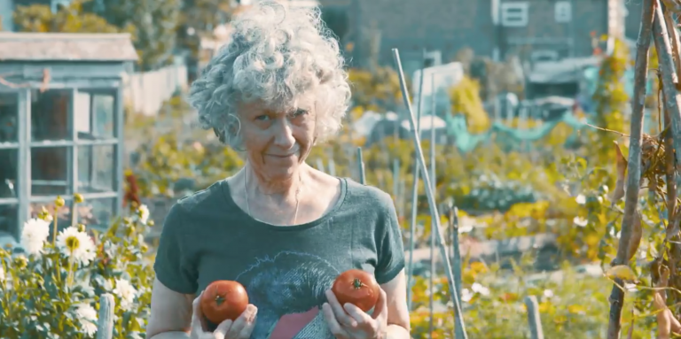 Karen Spicer, a petite woman with curly grey hair, holds two ripe tomatoes up in front of her chest, as she stands in her allotment.