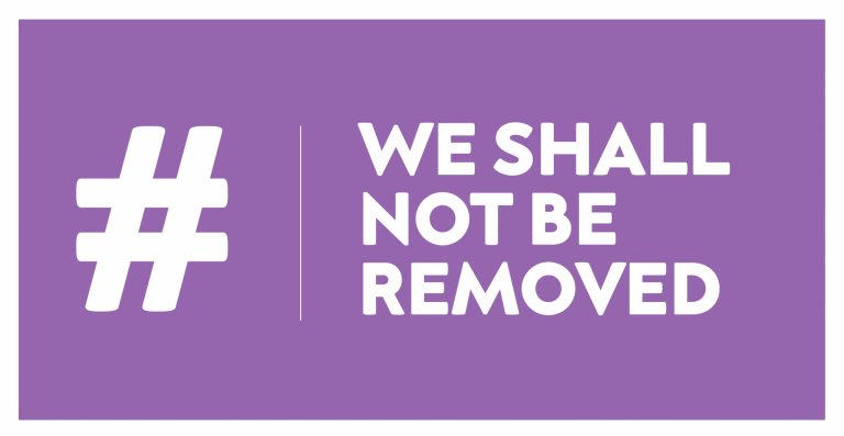 """""""#WeShallNotBeRemoved"""" written in bold capital letters on a purple background."""