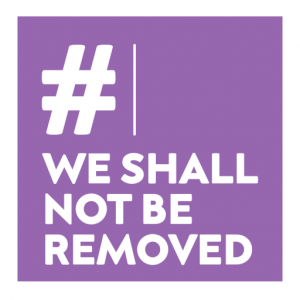 """Freedom Day image. """"#WeShallNotBeRemoved"""" written in bold strong white letter on a purple background."""