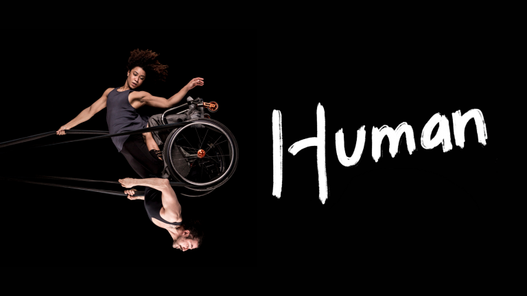 Black background. A photo of a woman and a man swinging in the air like a pendulum, looking powerful and graceful. They share a wheelchair which is held up in the air by black circus straps. She has frizzy brown hair, muscular arms and wears a grey tank top She is kneeling on his thighs and one of her arms holds the straps above her head while the other points down towards the floor. He has a neatly trimmed brown beard, muscular arms and wears a black tank top. He holds the straps to the sides of his chest with both hands. The image captures them at the highest point of the swing, to our right, bringing the man to an upside- down position with the woman above him. Their bodies are doing something hard, but their strength makes it look effortless. One word written in white, thick, brush-style letters above the photo: 'Human'.